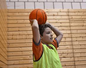 Junge spielt Basketball