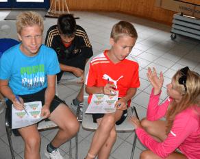 Trainerin erklärt Teilnehmern Ernährung - Move-It Sportcamps