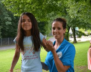 Trainerin hilft Teilnehmer auf Slackline - Move-it Sportcamps
